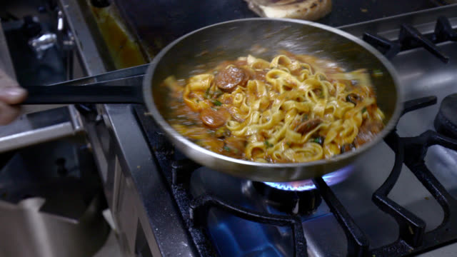 tossing pan with tagliatelle in tomato sauce with sausage - tagliatelle stock videos and b-roll footage