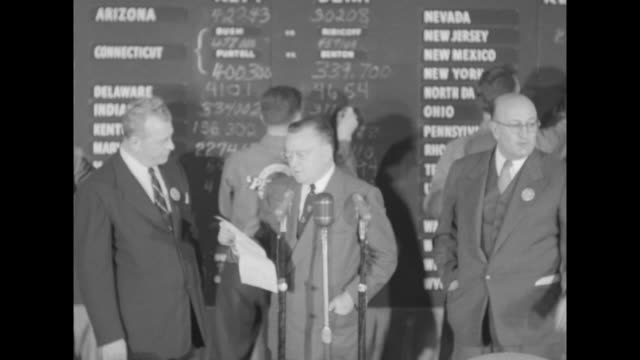 vídeos de stock, filmes e b-roll de tote board listing states with young men busily making chalk notations / men at microphones with sot dwight d eisenhower has been elected president... - florida us state