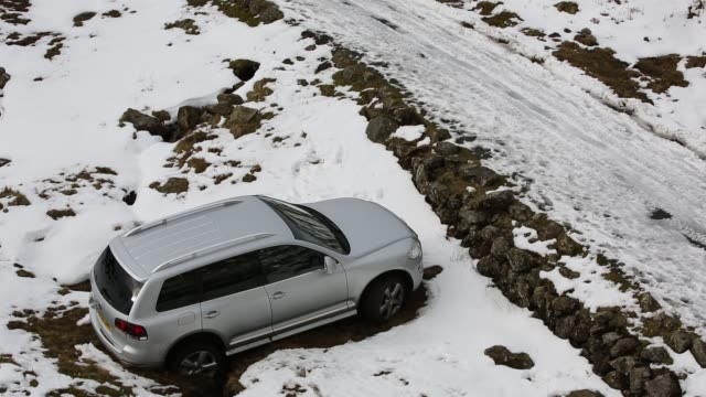 a vw touareg that slid off wrynose pass in the snow, lake district, uk. - rutschen stock-videos und b-roll-filmmaterial