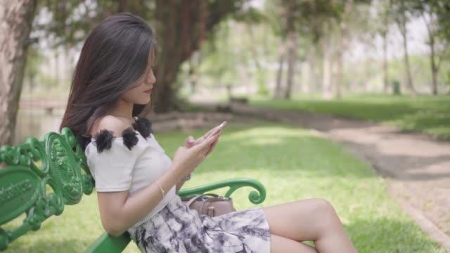 vídeos de stock, filmes e b-roll de toque de telefone sms, escrevendo, jovem garota no parque - visor digital