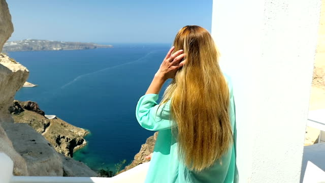 touching hair & looking at view - santorini stock videos and b-roll footage