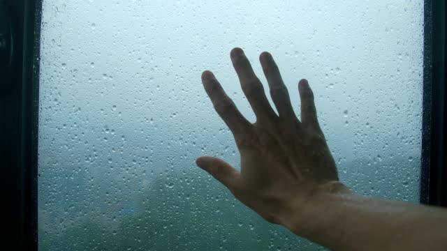 vidéos et rushes de toucher la fenêtre pluvieuse - buée