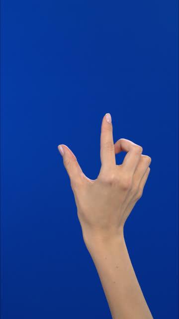 vídeos de stock, filmes e b-roll de touchscreen mão feminina mostrando gestos multitouch na tela azul. vídeo de formato vertical - pegada