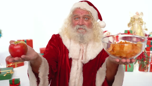 tough choice for santa claus - apple or chips - ascorbic acid stock videos & royalty-free footage