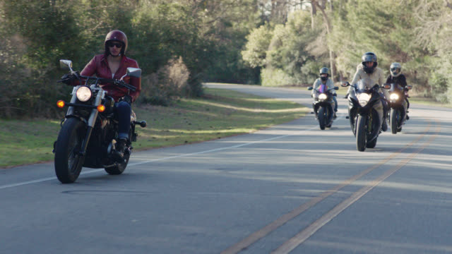 slo mo. tough girl in leather jacket leads the pack as group of women on motorcycles cruise down sunny highway. - motorradfahrer stock-videos und b-roll-filmmaterial