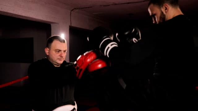 vídeos de stock, filmes e b-roll de lutador de caixa forte chute praticando com treinador - posição de combate