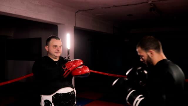 vídeos de stock, filmes e b-roll de lutador de caixa pontapé duro treinamento com instrutor - posição de combate