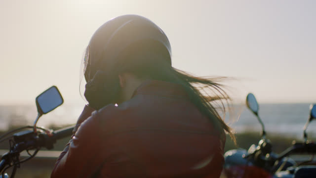 MS SLO MO. Tough woman on motorcycle pulls helmet on overlooking the ocean.