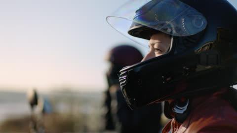 cu slo mo. tough woman pulls motorcycle helmet on by the ocean. - helmet stock videos & royalty-free footage