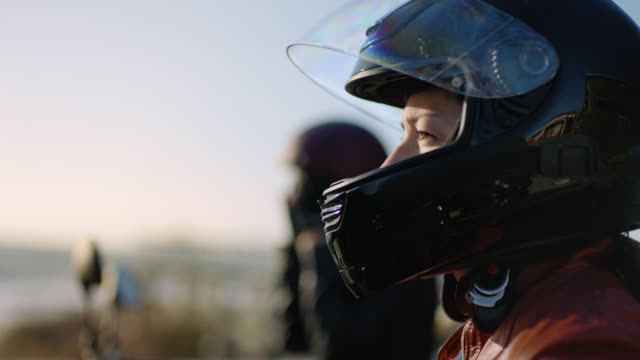 vídeos y material grabado en eventos de stock de cu slo mo. tough woman pulls motorcycle helmet on by the ocean. - casco de deportes