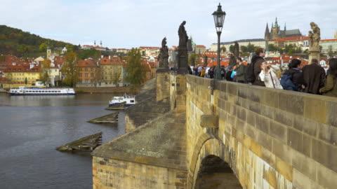 touirsts moving on prague charles bridge - 聖ヴィート大聖堂点の映像素材/bロール