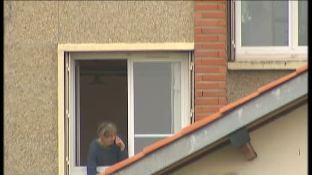 toulouse siege at home of suspected serial killer; ext elderly woman looking out of her window woman stands at window talking on mobile phone people... - トゥールーズ点の映像素材/bロール