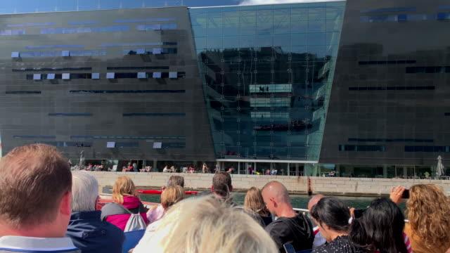 a tour boat and black diamond, the royal library, copenhagen - オーレスン地域点の映像素材/bロール