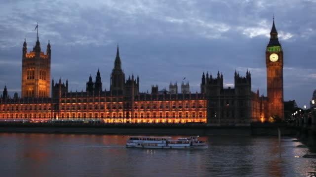 vídeos de stock, filmes e b-roll de a tour boat cruises past the houses of parliament and big ben. - passear sem destino