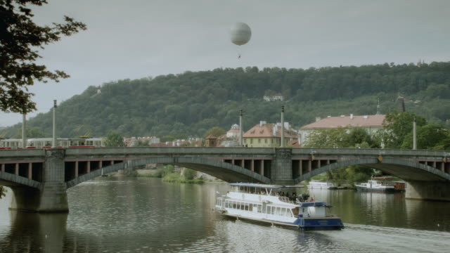 stockvideo's en b-roll-footage met ws tour boat cruising through a waterway under a concrete, arched bridge with a train traveling across while a hot air balloon is flying overhead in the distance - passagiersboot