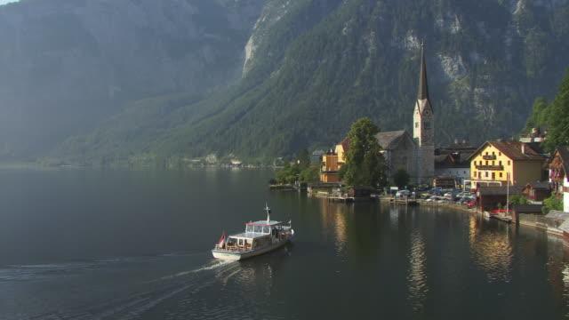 ws, ha, tour boat docking in port at village hallstatt, austria - österreichische kultur stock-videos und b-roll-filmmaterial