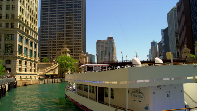 a tour boat glides along on the chicago river near downtown chicago, illinois. - dusable bridge stock videos & royalty-free footage