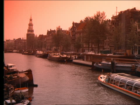 tour boat moving past docked boats in canal / amsterdam - ausflugsboot stock-videos und b-roll-filmmaterial