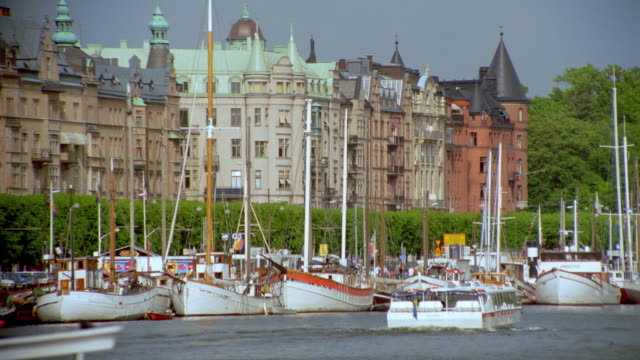 rear view tour boat moving toward docked sailboats at marina / stockholm bldgs in background / strandvagen - stockholm stock videos & royalty-free footage