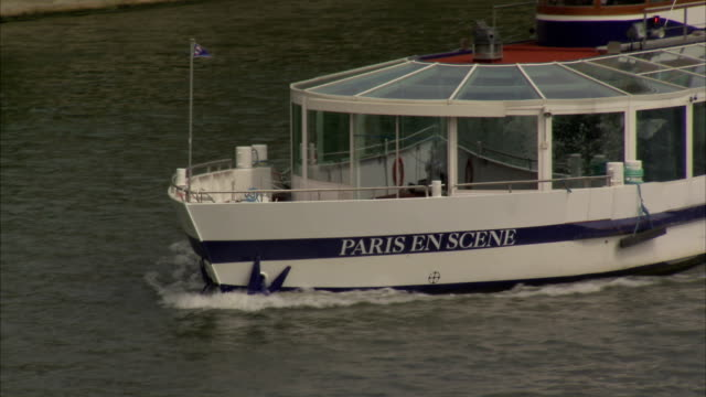 A tour boat named Paris en Scene glides down the water of the Seine in Paris. Available in HD.