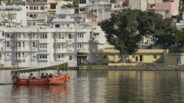A tour boat on Lake Pichola cruises past apartment buildings and hotels.