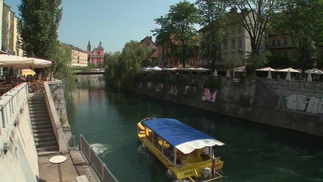 WS HA Tour boat on Ljubljanica River with Dvorni trg and Franciscan Church of Annunciation in background, Ljubljana, Slovenia
