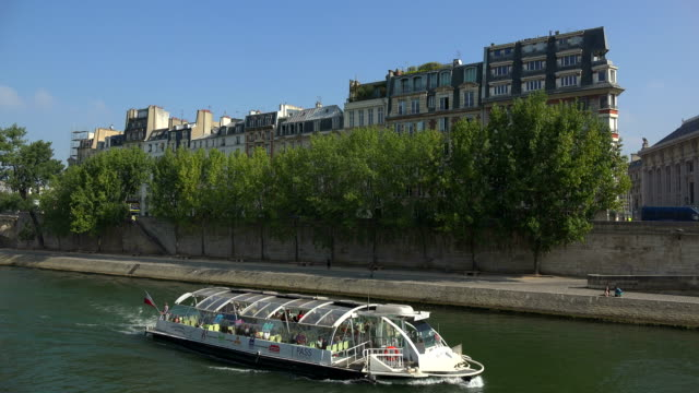 tour boat on seine river at quai des orfevres, ile de la cité, paris, ile de france, france - imbarcazione per passeggeri video stock e b–roll
