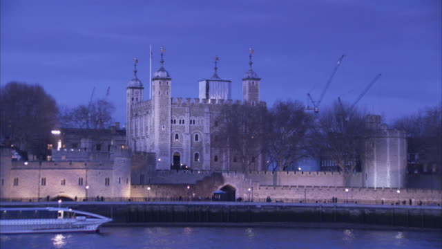 a tour boat on the river thames passes the tower of london. - fluss themse stock-videos und b-roll-filmmaterial