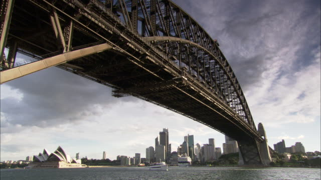 a tour boat slowly approaches sydney harbor bridge. - bennelong point stock videos and b-roll footage