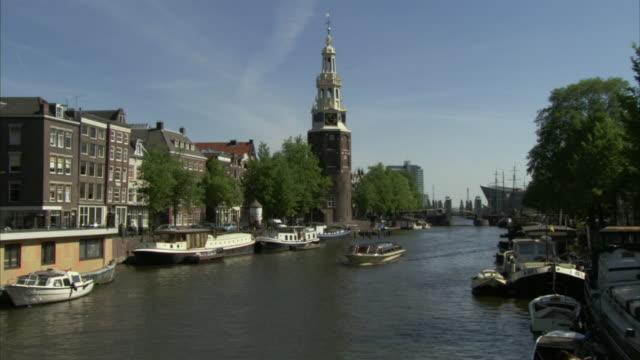 WS Tour boat traveling on Oude Schans canal near Montelbaanstoren / Amsterdam, Netherlands