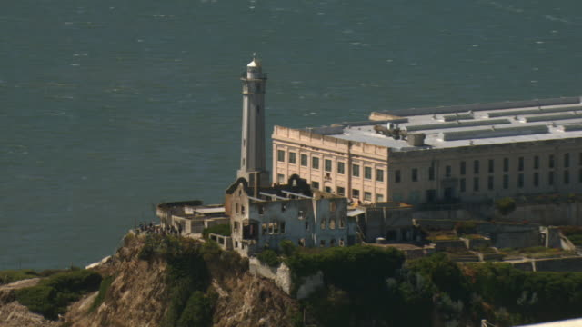 a tour boat waits alongside the coast of alcatraz island. - alcatraz island stock videos & royalty-free footage