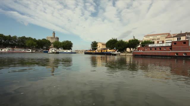 vidéos et rushes de ws tour boats moored on sete canal, tour de constance in background / aigues mortes, languedoc-roussillon, france - canal eau vive