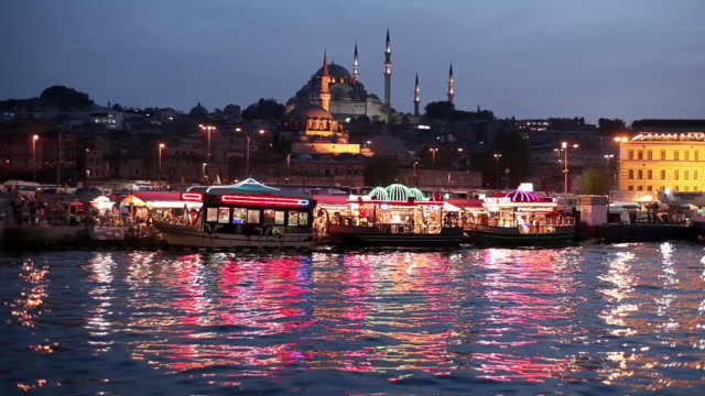 vídeos de stock e filmes b-roll de ws tour boats on golden horn with new mosque (yeni mosque) and suleymaniye mosque in background at dusk / istanbul, turkey - corno dourado istambul