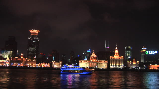 WS Tour boats passing on the Huangpu River at night with the Bund in the background/ Shanghai, China