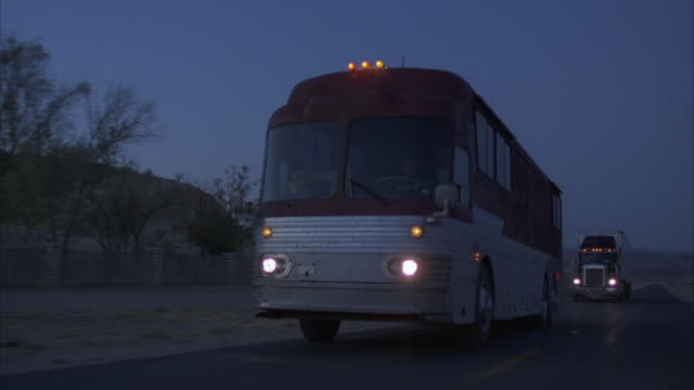 stockvideo's en b-roll-footage met rear pov, tour bus and truck driving on desert highway at dusk, usa - dubbeldekker bus