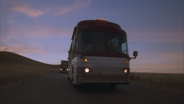 stockvideo's en b-roll-footage met rear pov, tour bus and truck driving through prairie at sunset, usa - dubbeldekker bus