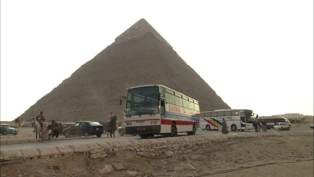 tour buses drive away from a pyramid in giza, egypt. - pyramid stock videos & royalty-free footage