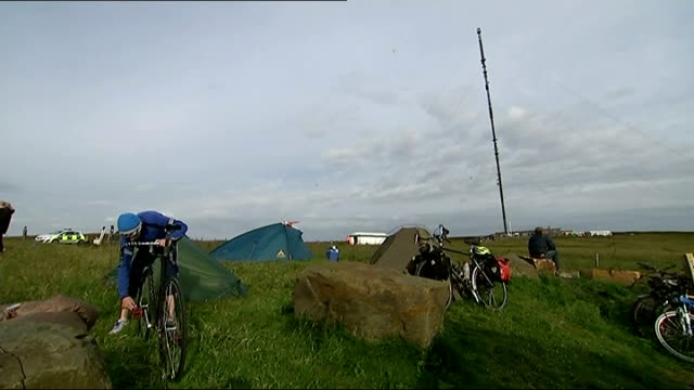 Holme Moss fans early morning ENGLAND West Yorkshire Holme Moss EXT Boy eating breakfast / various of people camping at side of road / cyclist...