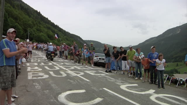 ws tour de france bike race on country road with spectators watching / alps, france - ツール・ド・フランス点の映像素材/bロール