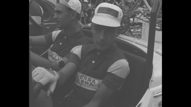 tour de france rides through rheims / cyclists resting before race starts / cyclists riding through town - ツール・ド・フランス点の映像素材/bロール