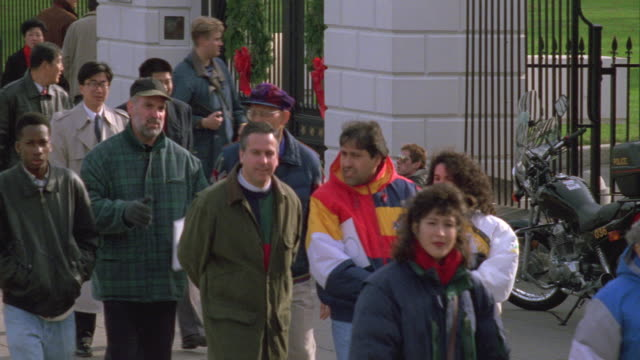 MS Tour groups passing white house gates (with Christmas wreathes on gates) / Washington D.C., United States