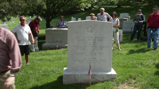 ws tour guide at the gravestone of the most decorated veteran as part of arlington national cemetery 150th anniversary commemoration the cemetery... - アーリントン国立墓地点の映像素材/bロール