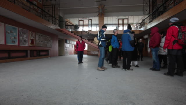 a tour guide telling the story of the abandoned public building in pyramiden, a soviet ghost town on the archipelago of svalbard - 2014 stock-videos und b-roll-filmmaterial