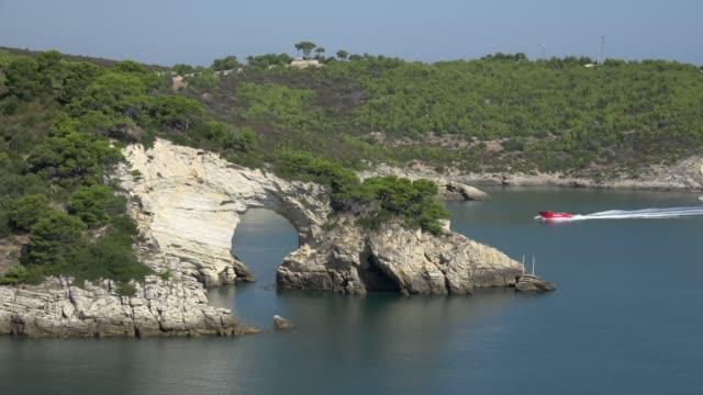 vídeos de stock e filmes b-roll de a tourboat at arco di san felice, natural archway at rocky coast with white limestone rocks - arco natural