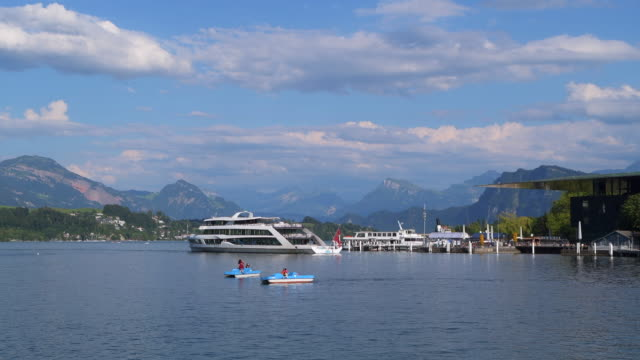 tourboat, boats and pedal boats on lake lucerne with lucerne culture and congress centre (on right side). lucerne, lake lucerne, canton of lucerne, switzerland. - lake lucerne stock videos & royalty-free footage