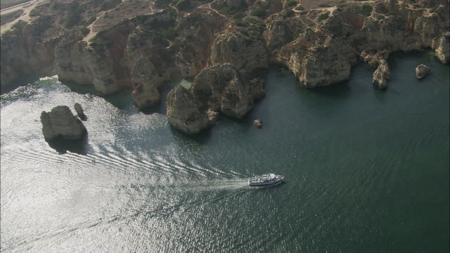 aerial ws tourboat moving along coastline with sea stacks / lagos, faro, portugal - tourboat stock videos & royalty-free footage