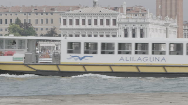 WS Tourboat moving in canal, buildings in background / Venice, Italy