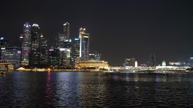 vídeos de stock e filmes b-roll de tourboat sailing in marina bay at night, singapore - barco de turismo
