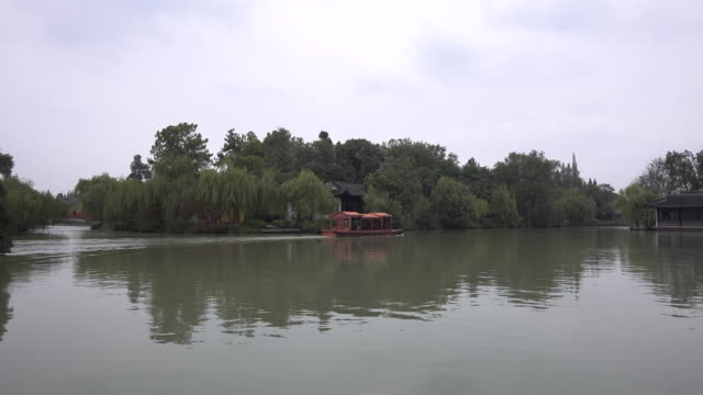 tourboat sails on yangzhou slender west lake yangzhou slender west lake or slim west lake is listed on unesco cultural heritage sites - tourboat stock videos & royalty-free footage