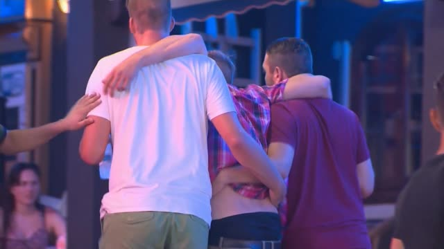 british police officers patrol in magaluf; night young women tourists waving to camera in street in bar and nightclub area of town young male tourist... - betrunken stock-videos und b-roll-filmmaterial